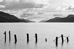 Dores Beach, Loch Ness (spodzone) Tags: camera old light sky blackandwhite sunlight art nature water monochrome beautiful lines clouds composition lens landscape photography scotland highlands dynamic emotion unitedkingdom horizon memories gimp places rules calm equipment zen vista balance beyond loch moment pentacon striking toned solitary contrasts tranquil contrejour lochness lump contentment lightanddark elegance shapely transience gbr dores nearfar digikam landwater olympuspenf skyearth shapeandform cloudappreciation rawconversion loosecomposition intimatelandscape pentacon50mm rawtherapee naturehappens mankindnature timefulness nearmidfardistance