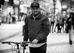 B is for Bicycle (Just Ard) Tags: street people blackandwhite bw white man black blancoynegro monochrome face hat bike bicycle person photography mono nikon eyecontact noiretblanc zwartwit candid 85mm d750 unposed  biancoenero sap pushing schwarzundweis justard