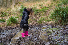 Child in mud on track through woodland (Ian Redding) Tags: wood pink black girl forest woodland walking outdoors happy track child mud boots path coat young dirty stepping messy wellingtonboots puddles wellies muddy