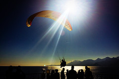 Liftoff (Melissa Maples) Tags: cameraphone winter sea sun mountains reflection apple water silhouette turkey asia mediterranean trkiye sunny antalya lensflare flare paragliding paraglider parachute sunflare iphone  iphone6