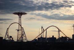 Coney Island at dusk (Milou Diable) Tags: newyorkcity carnival sunset sea sky newyork beach silhouette brooklyn clouds coneyisland seaside fairground dusk silhouettes fair lookup rides rollercoaster funfair