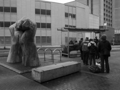 Queue (The6millionpman) Tags: street people monument wet monochrome statue wales blackwhite cardiff streetphotography olympus busstop queue damp olympusomdem5