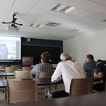 Students and professors watch a video together in a classroom.