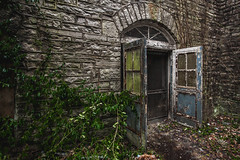 This loneliness won't last for long (Erin Watson/Abandoned Exploration) Tags: door old travel windows light shadow urban usa castle history abandoned broken nature overgrown leaves stone america canon dark outside photo back moss midwest closed peeling paint arch photographer exterior open darkness outdoor decay empty united explorer neglected over ruin arc entrance vine screen dirty historic adventure explore climbing growth dirt doorway fairy forgotten porn states exit mold grime taking exploration tale decayed ue peely erinwatson erinwatsonphotography
