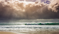 Rays of light breaking through brooding storm clouds over Catherine Hill Bay beach (kylieardill) Tags: ocean blue light sky storm beach water clouds sand waves wave shore nsw newsouthwales sunrays sunbeams raysoflight catherinehillbay