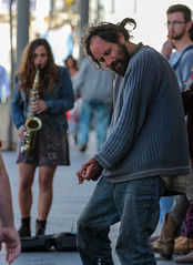 A young lady, with a sax. and in mini, can cause a man do all sorts of odd things (ybiberman) Tags: man girl dreadlocks israel dress dancing market candid jerusalem homeless band streetphotography mini saxophone sanity machneyehuda