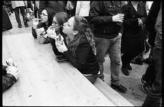 (Eating Is Making Love) (Robbie McIntosh) Tags: leica girls blackandwhite bw woman film monochrome analog 35mm candid strangers streetphotography sausage rangefinder chips bn summicron negative analogue wurst streetfood m2 ilford fp4 biancoenero argentique leicam2 fingerfood dyi wurstel selfdeveloped ilfordfp4 pellicola analogico sunny16 nometering leicam filmisnotdead autaut leicasummicron35mmf20iv guessexposure summicron35mmf20iv leicasummicron35mmf2i internationalstreetfoodfestival arsimagofd arsimagofddeveloper