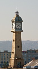 Barceloneta's Clock Tower (Torre del Rellotge) and former light house in the port of Barcelona