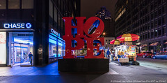 Hope (DSC04746) (Michael.Lee.Pics.NYC) Tags: sculpture newyork night hope cityscape sony bank chase hotdogs publicart atm streetvendor robertindiana voigtlanderheliar15mmf45 a7rm2