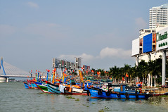 Boats and billboards (Roving I) Tags: architecture advertising holidays apartments bridges flags vietnam billboards fishingboats danang promotions hanriver azura fleets