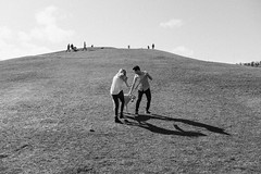 Heather and Eric try to wrangle Crosby for a photo on Kite Hill at Gas Works Park. Seattle, WA. March 2016. (poopoorama) Tags: seattle blackandwhite dog washington engagement eric unitedstates heather fujifilm gasworkspark crosby xseries dannyngan laboradoodle wclx100 x100t dannynganphotography