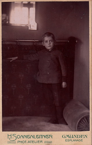 Portrait of a young boy [with face of photographer reflected in mirror] by H. Sonnenleitner (c.1915)