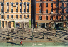 The Little People (Dorchester (Mildred Alpern)) Tags: nyc people cars buildings outdoors shadows rooftops sidewalk bicyclist storefronts stores fireescapes bicyclelane passersby