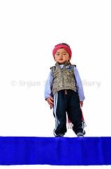 Little Bhutanese boy playing against white wall (Shutter Shooter) Tags: travel boy white playing tourism wall kid tour bhutan little sweet buddha buddhist fulllength young buddhism hideandseek thimpu isolated bhutanese lowangle thimphu mischiveous piller 2013