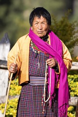 Prayer beads (Gabriela Iacobuta) Tags: old pink sun thread yellow lady female scarf religious beads asia bhutan buddha traditional prayer religion praying ngc sunny buddhism stick dzong fortress hymalaya punakha 5photosaday