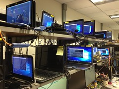 The life of an expert...  Pt 1: darkness in the middle of the shelf (wbaiv) Tags: lab work computers office indoor workplace electronics benches shelves cables laptops towerboxes desktops setup remote access lan network switches tech technology telepresence workersresource farm collection site windowless closed artificial light fluroescent mouse trackpad desk automation modern tools workshop space organization