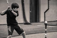Eyes on the Ball (HopesPhotos) Tags: blackandwhite concentration blackwhite nikon baseball d750 odu battingcage kidssports hittingofftee nikond750 baseballdrill