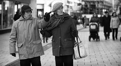 There's The Hat Shop (Just Ard) Tags: street people blackandwhite bw woman white man black blancoynegro monochrome face hat person photography mono nikon noiretblanc zwartwit candid 85mm older d750 unposed pointing  biancoenero schwarzundweis