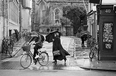Rainy day (V Photography and Art) Tags: street people church rain bicycle umbrella wind streetlamp candid streetphotography oxford sheltering