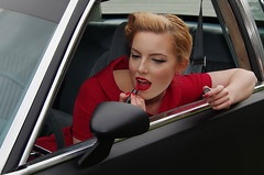 Last moment touch-up (Jumpin'Jack) Tags: red portrait woman black colour girl car mirror view vibrant rear makeup vivid hairdo retro fixing lipstick ina pinup oldsmobile applying ofa witha