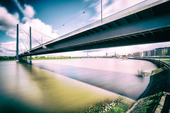 a Dsseldorf afternoon (Blende57) Tags: city longexposure bridge sky water clouds river landscape flow cityscape crossing wideangle bluesky sight dsseldorf rhine duesseldorf sights rivercrossing rhinebridge rhineembankment cityofduesseldorf