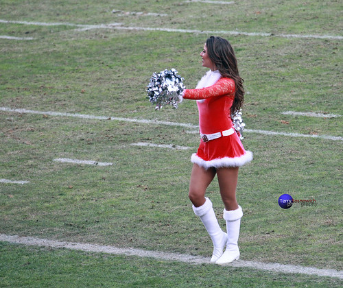 Redskinette Cheerleader on the field in Christmas outfit.