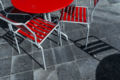 Red table and chairs (on Explore) (Jan van der Wolf) Tags: street shadow red composition table grey shadows chairs terrace denhaag tiles redrule schaduw rood terras tafel straat tegels stoelen compositie map152106v