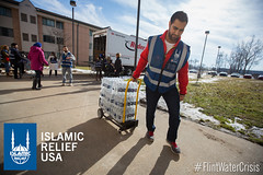 Islamic Relief USA volunteer pulls cases of water into an apartment building that is part of the government housing projects in Flint.