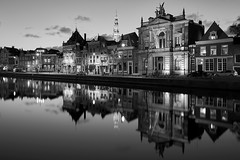 Old Treasures (McQuaide Photography) Tags: old city longexposure light blackandwhite bw house holland reflection building history haarlem water netherlands spaarne monochrome dutch skyline museum architecture zeiss river outside mono evening licht blackwhite still twilight lowlight europe outdoor dusk sony tripod nederland peaceful oldbuildings calm historic spire fullframe alpha huis avond residential oud tranquil grotekerk stad manfrotto noordholland gebouw dewaag c1 huizen rivier teylersmuseum 1635mm northholland phaseone variotessar captureone mirrorless sonyzeiss groteofstbavokerk mcquaidephotography a7rii ilce7rm2 captureonepro9
