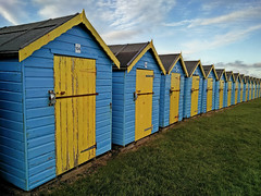 Time rusting away their thin hinges (@sage_solar) Tags: blue roof england sky green beach grass yellow clouds sussex day doors westsussex shed huts hut beachhut beachhuts 104 sheds bognorregis hinges felpham