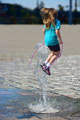 Jump (swong95765) Tags: water fountain girl hoop jump outdoor midair airborne leap hulahoop acrobatic waterjet