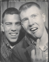 Photo booth portrait of two men flipping off the camera (simpleinsomnia) Tags: old white man black monochrome vintage booth found photo blackwhite funny photobooth antique snapshot young off photograph vernacular unusual flippingoff youngman flipping foundphotograph