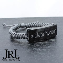 """A custom carbon fiber bracelet. """"A clear horizon"""" in silver with a charcoal grey band. Big Thanks to @marshpowerhousefab for spraying the custom text & @turbocarbon for the carbon fiber. #jenniferrayjewelry #jrjcarbon #carbonfiber #carbonfibre #aclearhori (JenniferRay.com) Tags: ray jennifer jewelry carbon custom fiber exclusive paracord jrj instagram"""