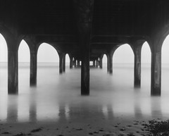 Under the Pier (Attila Pasek) Tags: sea bw film beach pier scan xray 4x5 largeformat graflex speedgraphic longexposuretime boscombepier pacemaker kodakektar 127mmf47