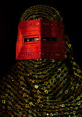 a bandari woman wearing a traditional mask called the burqa, Hormozgan, Minab, Iran (Eric Lafforgue) Tags: red portrait people woman beauty vertical golden persian clothing eyes asia veil mask iran muslim islam religion hijab culture persia headshot hidden indoors covered iranian adultsonly oneperson traditionaldress burqa customs middleeastern frontview sunni burka chador 20sadult youngadultwoman balouch darkbackground hormozgan onewomanonly lookingatcamera burqua  bandari  1people  iro thursdaymarket  minab colourpicture  borqe panjshambebazar boregheh irandsc067132
