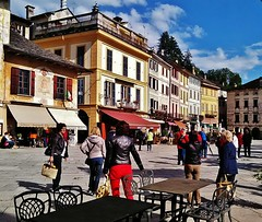 the town square (SM Tham) Tags: trees sky people italy buildings square outdoors town cafe chairs facades tourists tables shops awnings canopies lakeorta italianlakes ortasangiulio piazzamotta