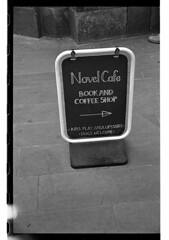 Novel Cafe (Man with Red Eyes) Tags: street film monochrome sign analog advertising blackwhite kodak pavement rangefinder lancaster nikkor tmax400 handwritten 50mmf14 aboard homedeveloped silverhalide pyrocathd bessar2s