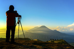 silhouette nature photographer in action during sunrise (sydeen) Tags: camera travel blue light sunset sky orange sun sunlight mountain nature beautiful silhouette yellow horizontal fog sunrise indonesia landscape person evening countryside stand high warm solitude photographer view outdoor body background horizon tripod picture dramatic adventure mount photograph land prau