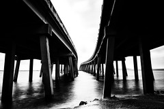 Under the Bridges (cylynex) Tags: longexposure blackandwhite water monochrome underpass highway florida bridges sharp bleak destin
