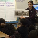 A student reading to elementary students in a classroom