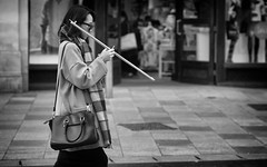 The Mobile Stick Carrier (Just Ard) Tags: street people blackandwhite bw woman white black blancoynegro girl monochrome face mobile person photography mono sticks nikon phone noiretblanc zwartwit candid 85mm d750 unposed  biancoenero schwarzundweis justard
