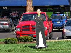 He doesn't look very happy on the deadline to file taxes. (kennethkonica) Tags: travel blue windows shadow red usa color green grass car america truck canon spring midwest traffic jeep random outdoor indianapolis wheels vivid indy bowtie indiana sunny pickup cardboard vehicle dodge ram global parkinglots canonpowershot hoosier marioncounty hrblock taxreturns fakeperson dodgetough