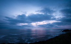 Asleep on the Horizon (Gabriel Tompkins) Tags: ocean blue sunset sky panorama usa sun seascape water backlight clouds oregon america skyscape landscape twilight nikon colorful soft pacific cloudy dusk vibrant calming lavender peaceful wideangle calm pacificnorthwest oregoncoast backlit nikkor dslr lowkey pnw 2009 cloudscape oregonstate gloaming 18105 d90 18105mm nikond90 18105mmf3556gvr tronam gabrieltompkins tronamcom