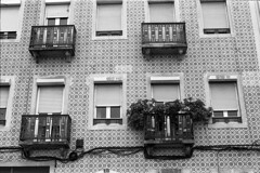 Balconies and windows of Lisbon (Ninoo Vita) Tags: windows white black misty rollei photography 50mm lights lightsandshadows shadows gloomy shot pentax lisbon overcast balconies epson 100 asa dim rodinal schwarzweiss somber mx murky schwarz dingy drab 114 darkened shadowy pentaxmx smcm weis nocolor r09 v750 rpx epsonv750 inspirationalphotography blackwhitepassionaward emozioniinbiancoeneroemotionsinblackandwhite pentaxsmcm11450mm yourperspectiveandcreative