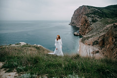 Lady of the windy shores (Alex Karamanov) Tags: ireland light sea portrait people cliff seascape black mountains color art water girl rock lady landscape seaside hands mood wind outdoor atmosphere indoor her shore melancholy crimea vsco