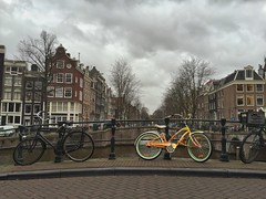 Bright bike on a grey day  (farflungistan) Tags: bridge winter holland netherlands amsterdam bike yellow clouds canal cityscape rainyday nederland streetphotography fiets amsterdamcanals