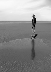 Standing (Andrew Gibson.) Tags: sea sky blackandwhite bw men beach water statue liverpool coast sand waves alone tide statues castiron crosby antonygormley sefton anotherplace crosbybeach siranthonygormley sonya7ii