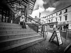 Ste(e)ped in thought (pootlepod) Tags: life street windows light sky blackandwhite woman white black color colour reflection girl monochrome station female clouds contrast mall dark naked advertising lite photography climb sweater waiting sitting pants pavement candid steps perspective billboard sidewalk jeans tired jumper pullover spoons wetherspoons fedup hoardings canon60d stphotographia