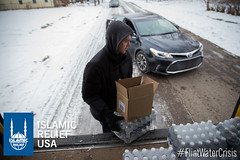 American Red Cross volunteers work with Islamic Relief USA to help distribute water bottles to residents of Flint.