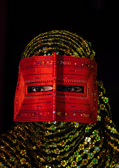 a bandari woman wearing a traditional mask called the burqa, Hormozgan, Minab, Iran (Eric Lafforgue) Tags: red portrait people woman beauty vertical closeup golden persian clothing eyes asia veil mask iran muslim islam religion hijab culture persia headshot hidden indoors covered iranian adultsonly oneperson traditionaldress burqa customs middleeastern frontview sunni burka chador 20sadult youngadultwoman balouch darkbackground hormozgan onewomanonly lookingatcamera burqua  bandari  1people  iro thursdaymarket  minab colourpicture  borqe panjshambebazar boregheh irandsc06708